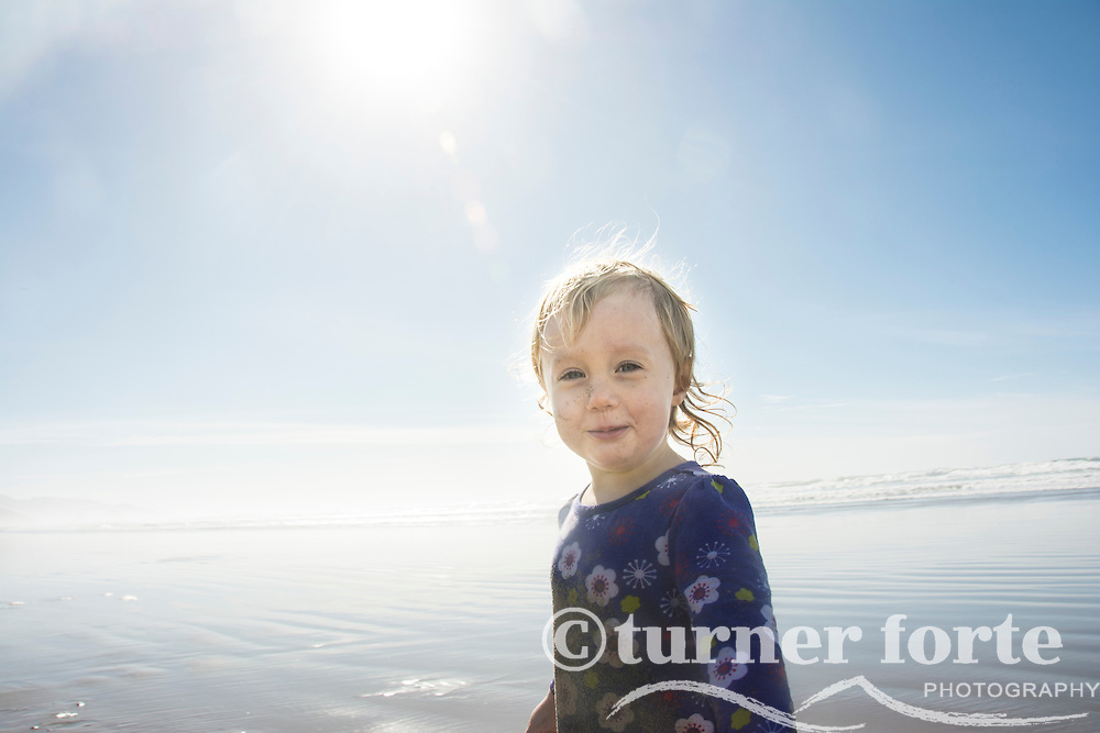 Portrait of happy toddler girl with sun flare on Cannon Beach, Oregon.