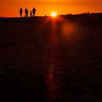 Sunset at Walberswick in Suffolk England with a family in silhouette