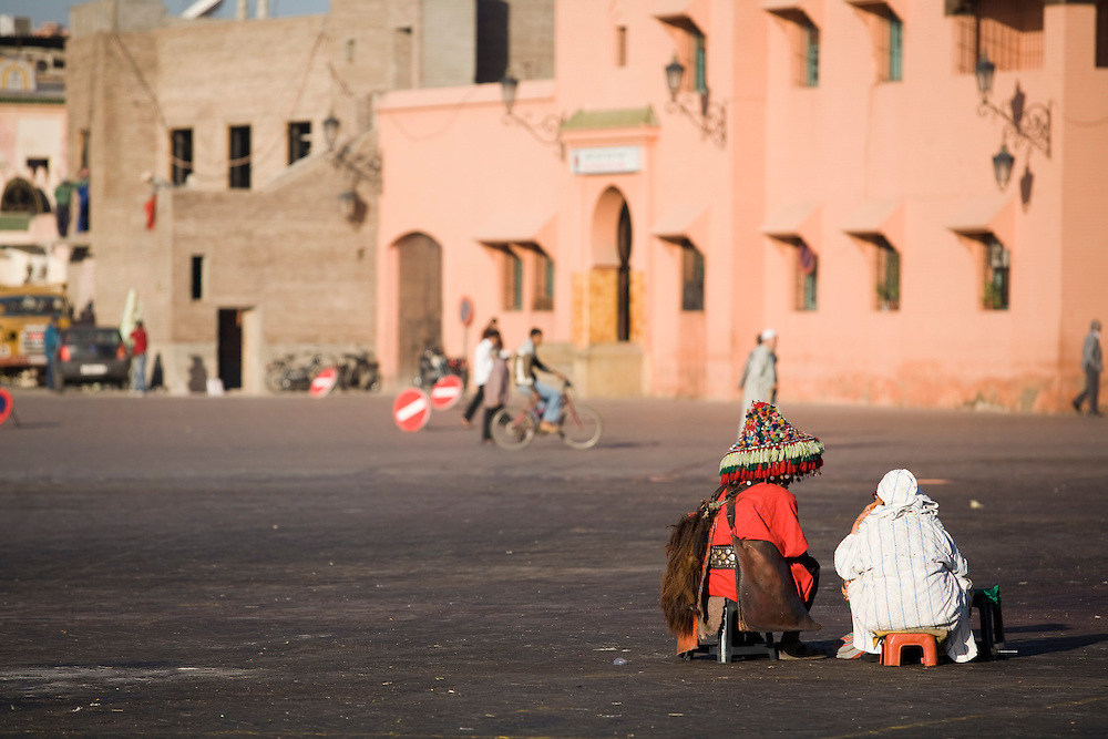 A water man and a street vendor arrive early in the morning at Djemaa el Fna in anticipation of a busy day of tourists