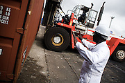 A tractor carries containers to be loaded aboard a cargo boat at the sea port in Lome, Togo on Friday October 3, 2008.