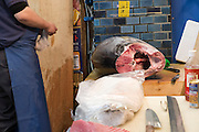 Fishmonger cuts tuna fish for sale at the Tsukiji fish market, largest in the world, Tokyo, Japan