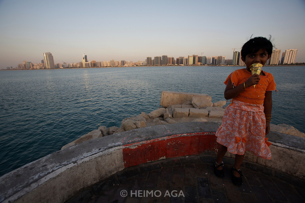 Panoramic view of the Corniche from the Breakwater. Little girl of an Indian guest worker having an ice cream cone while curiously gazing at the photographer.