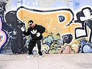Street rapper dancing  near a graffited wall