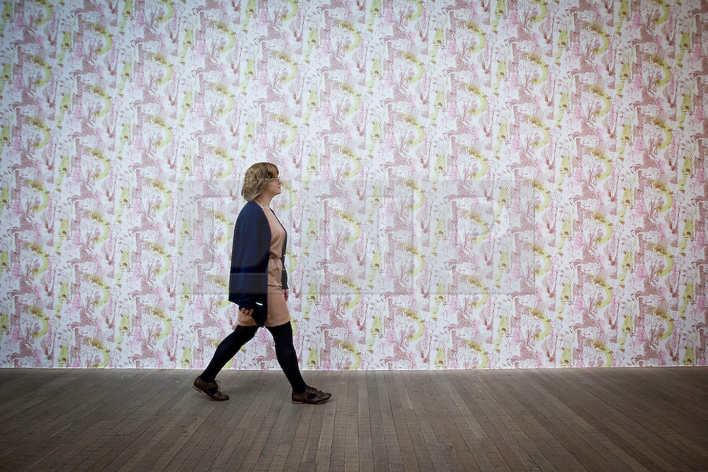© Licensed to London News Pictures. 13/11/2012. London, UK. A member of Tate Modern staff walks past wallpaper entitled 'Jay and Jay' (2012) by French artist Marc Camille Chaimowicz at the press view for a new exhibition at the Tate Modern in London today (13/11/12) . The exhibition, 'A Bigger Splash: Painting After Performance', takes a look at the relationship between painting and performance, bringing together the works of over 40 artists, including Jackson Pollock and Cindy Sherman, and runs from the 14th of November 2012 to the 1st of April 2013.  Photo credit: Matt Cetti-Roberts/LNP