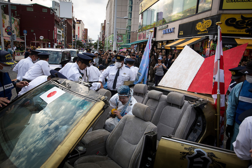 OKINAWA, JAPAN - JANUARY 8 : Japanese police try to control new adults in a vehicle showing off with loud megaphones in Kokusai dori after attending a Coming of Age Day celebration ceremony in Okinawa, Japan on January 8, 2017. The Coming of Age Day, one of the Japanese national holidays, is the day to celebrate young people who have reached the age of 20, the age of maturity in Japan, when they are legally permitted to smoke, drink alcohol and vote. (Photo by Richard Atrero de Guzman/NURPhoto)