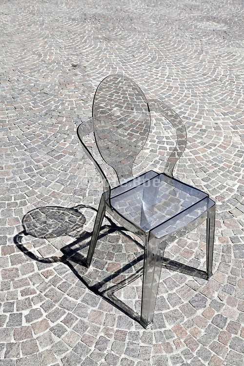 grey transparent chair with its shadow on cobble stone pavement