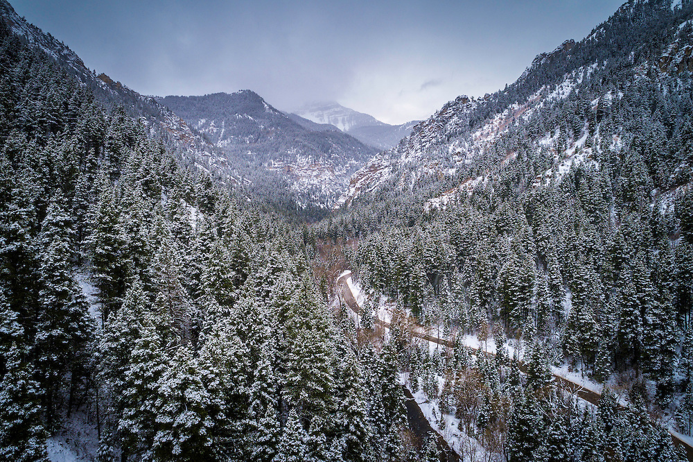 An aerial view of a snowy Winter day in American Fork Canyon as the snow covers the trees and continues to fall.