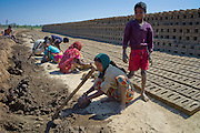 Indian family making bricks made from mud clay at Khore Bricks Factory, Rajasthan, Northern India