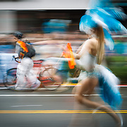 A woman dressed in brightly colored feathers walks the parade route of the Solstice Parade in Seattle Washington.