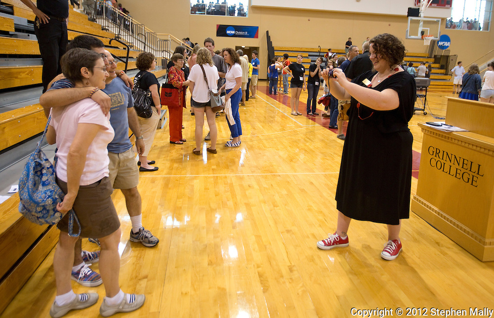 Andrea Conner (right), Assistant Dean of Students and Director of Residence Life and Orientation, takes a photo of a new student and his parents after the end of the New Student Orientation Welcome Ceremony in the Darby Gymnasium at Grinnell College in Grinnell, Iowa on Saturday, August 25, 2012.