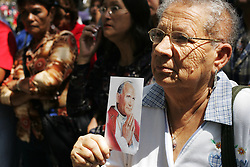 People, some holding images of the Pope, pray outside during a mass in honor of Pope John Paul II. In 2005, Latin America was home to about 40% of the world's Catholics.  It is a region where Catholicism is strong and has room to grow, making many analysts wonder if a future Pope will come from a Latin American country.
