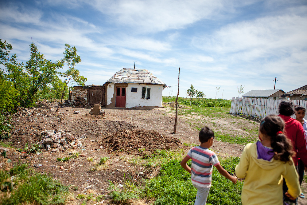 A family walking in the Roma area of Frumusani. In Frumusani, the Roma Education Fund—supported by the World Bank, Open Society Foundations, the European Union, and other donors—is working to remove the barriers local Roma children face to complete their primary school education.