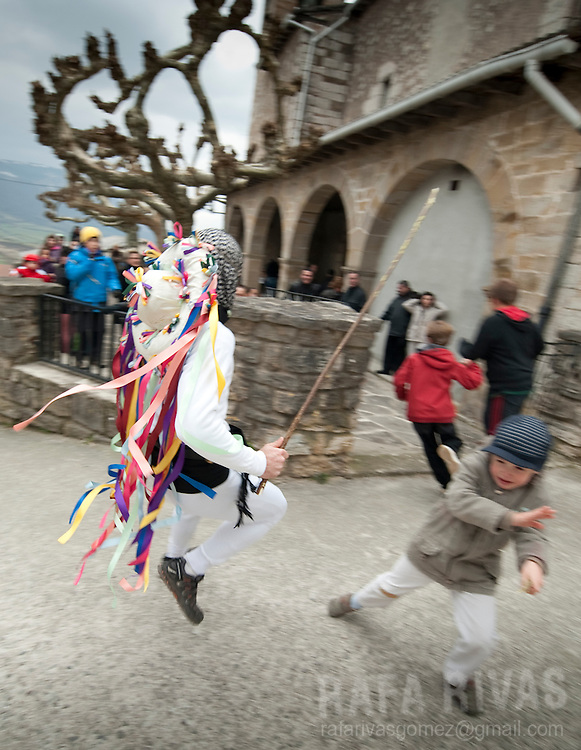 A momotxorro chases children during the ancient carnival of Unanu, North of Navarra province in Spain, on March 8, 2011. Momotxorros chase locals and slash them with sticks.  PHOTO/ RAFA RIVAS