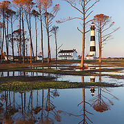 While these trees are no longer standing, visitors to this iconic North Carolina coastal lighthouse once traveled around a circular entrance of tall trees.  Often, following heavy rains, the circle would inundate with water and provide endless opportunities for reflection photography.  On this particular evening, the last light was catching the tree tops and reflecting into the rain puddle.