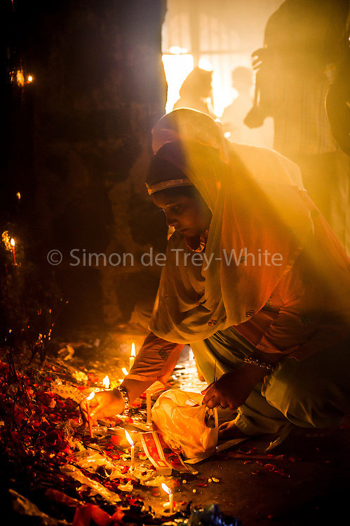 2nd April 2015, New Delhi, India. Believers light candles and incense sticks at a shrine dedicated to Djinn worship in the ruins of Feroz Shah Kotla in New Delhi, India on the 2nd April 2015<br /> <br /> PHOTOGRAPH BY AND COPYRIGHT OF SIMON DE TREY-WHITE a photographer in delhi<br /> + 91 98103 99809. Email: simon@simondetreywhite.com<br /> <br /> People have been coming to Firoz Shah Kotla to leave written notes and offerings for Djinns in the hopes of getting wishes granted since the late 1970's. Jinn, jann or djinn are supernatural creatures in Islamic mythology as well as pre-Islamic Arabian mythology. They are mentioned frequently in the Quran  and other Islamic texts and inhabit an unseen world called Djinnestan. In Islamic theology jinn are said to be creatures with free will, made from smokeless fire by Allah as humans were made of clay, among other things. According to the Quran, jinn have free will, and Iblis abused this freedom in front of Allah by refusing to bow to Adam when Allah ordered angels and jinn to do so. For disobeying Allah, Iblis was expelled from Paradise and called &quot;Shaytan&quot; (Satan).They are usually invisible to humans, but humans do appear clearly to jinn, as they can possess them. Like humans, jinn will also be judged on the Day of Judgment and will be sent to Paradise or Hell according to their deeds. Feroz Shah Tughlaq (r. 1351&ndash;88), the Sultan of Delhi, established the fortified city of Ferozabad in 1354, as the new capital of the Delhi Sultanate, and included in it the site of the present Feroz Shah Kotla. Kotla literally means fortress or citadel.
