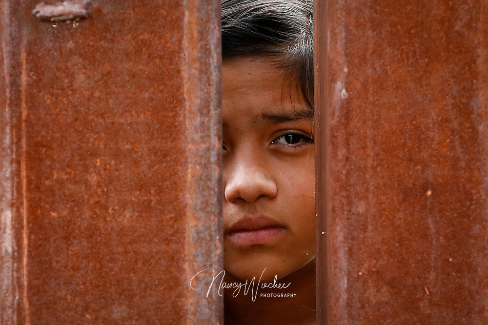 A Mexican girl peers through the fence during Mass at the international border in Nogales, Arizona, Oct. 23. Dioceses Without Borders, an effort of the dioceses of Nogales, Tucson and Phoenix, organized the liturgy celebrated on both sides of the U.S.-Mexico border. (CNS photo/Nancy Wiechec)