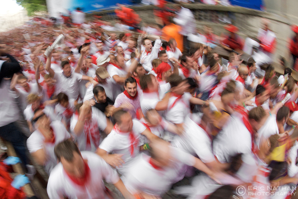 Crowds running in the encierro (bull run) during the annual festival of San Fermin (aka the running of the bulls) in Pamplona, Spain.