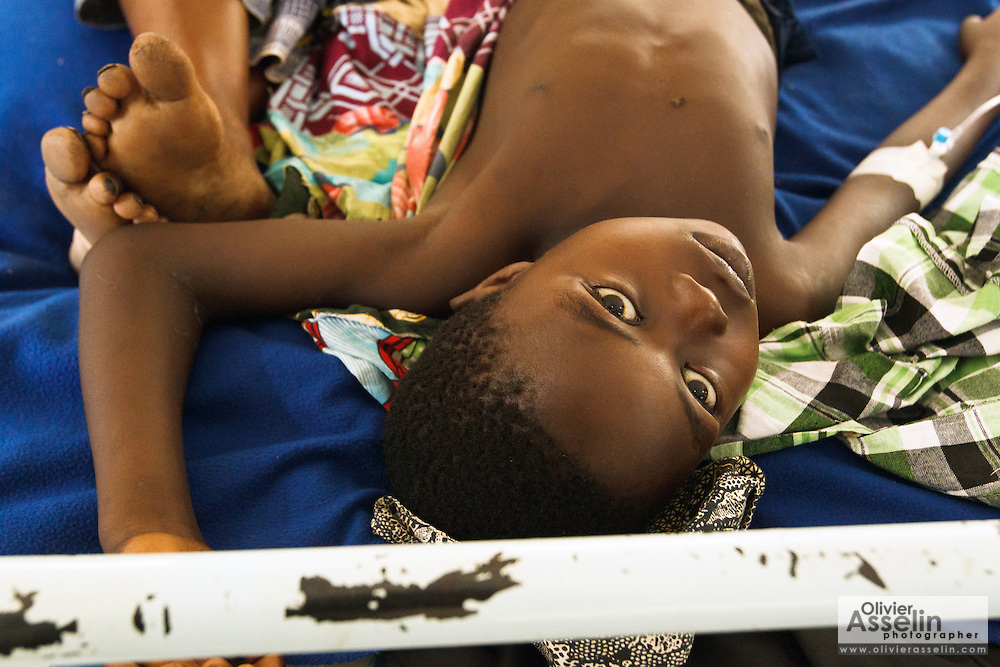 A boy who suffers from malaria lies on a bed in a clinic run by MSF next to the Tabacongo health center, in the town of Tabacongo, Katanga province, on Sunday February 19, 2012.