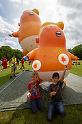 Children sitting with their official crowdfunder balloons in front of  the six metre high inflatable TrumpBaby balloon and the three metre high mini Trump Baby at the demo on the Meadows in Edinburgh, Scotland. United Kingdom. 14th July 2018.  (photo by Andy Aitchison / Trump Baby Sitters)