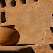 A clay pot on an adobe landing next to steps. Taken at Tumacacori Mission in Southern Arizona.