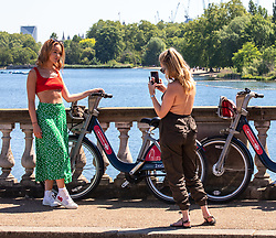 © Licensed to London News Pictures. 19/05/2020. London, UK. Two women pose for pictures on Serpentine Bridge in the sunshine in Hyde Park as weather experts predict a high of 27c this week. Last week the Government eased the law on lockdown to let people spend more time outside. Photo credit: Alex Lentati/LNP