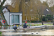 © Licensed to London News Pictures. 05/01/2014. Shepperton, UK A man in a boat sails past a house surrounded by water whilst gees feed in the floodwater. Rising river levels in the River Thames at Shepperton Lock in Surrey threaten local housing along the river today 5th January 2014. Britain is experiencing flooding and more heavy rain is expected. Photo credit : Stephen Simpson/LNP