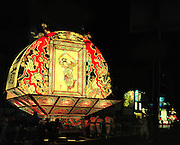 The Hirosaki  Neputa  festival in northern Japan. These floats are made from wooden frames which are covered with rice paper that has been hand painted. The floats are generally fan-shaped, with two flat sides. One portrays a historical battle scene with samurai fighting while the reverse shows a beautiful woman, often framed by scenes of death. The floats are pulled and some carried through the streets over a period of one week, each summer. Each float has members that do the pulling and carrying and other members that play the flute, drums, and other musical instruments.