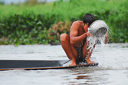 A boy on Burma's Inlé Lake bathes with a steel bowl on the bow of his longtail boat