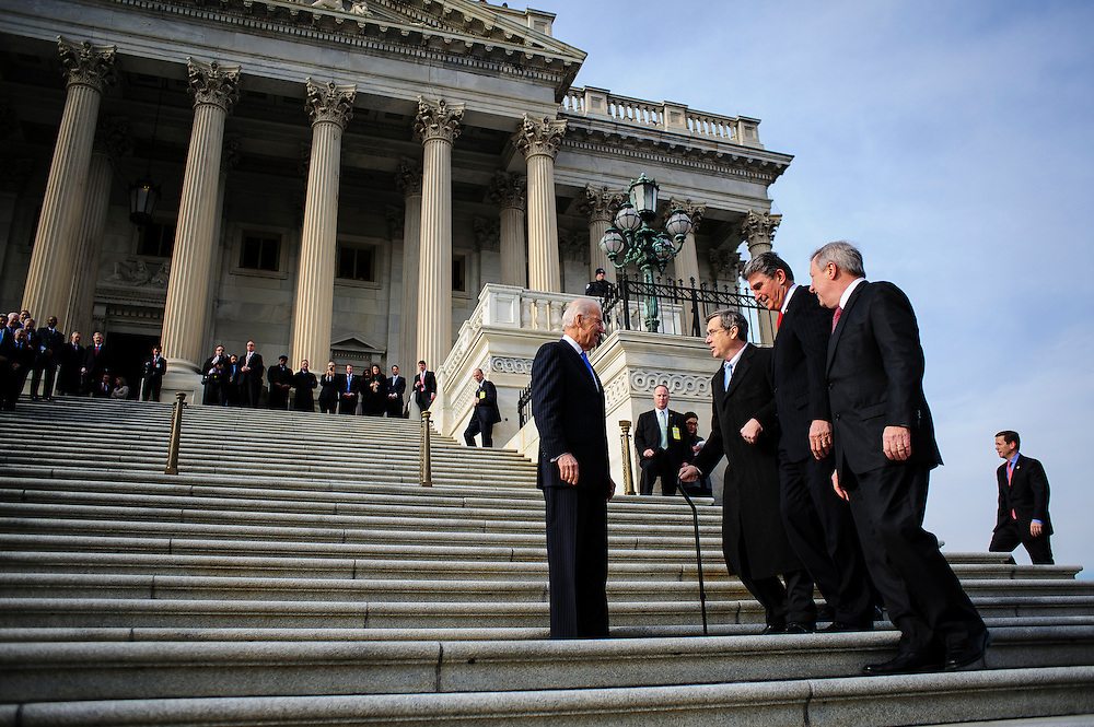 Vice President Joe Biden and Senators Joe Manchin (D-WV) and Dick Durbin (D-IL) greet Senator Mark Kirk (R-IL) as he makes his return to Congress at the U.S. Capitol in Washington, District of Columbia, U.S., on Thursday, Jan. 3, 2013. Kirk, 53, climbed the steps at 10:30 a.m. accompanied by Vice President Joe Biden and Senator Dick Durbin (D-IL). The 133th Congress begins Thursday with the swearing in of newly elected Members of Congress and the election of the Speaker of the House of Representatives. Photographer: Pete Marovich/Bloomberg