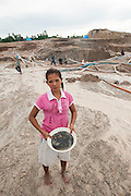 Yanti (22 years old). She stopped school at age 12 to work in the mine. . <br /> The tin ore she found is kept in a bowl. <br /> Illegal tin mine in Batako, Tunghin. Bangka Island (Indonesia) is devastated by illegal tin mines. The demand for tin has increased due to its use in smart phones and tablets.<br /> <br /> Yanti (22 ans). A arreté l'ecole a l'age de 12 ans. Pour se consacrer à la recherche d'étain. <br /> Mine d'étain illégale à Batako - Tunghin. <br /> L'île de Bangka (Indonésie) est dévastée par des mines d'étain sauvages. la demande de l'étain a explosé à cause de son utilisation dans les smartphones et tablettes.