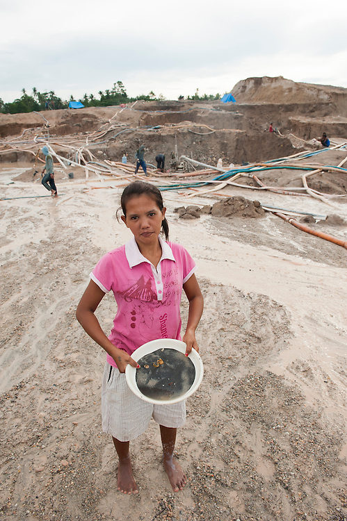 Yanti (22 years old). She stopped school at age 12 to work in the mine. . <br /> The tin ore she found is kept in a bowl. <br /> Illegal tin mine in Batako, Tunghin. Bangka Island (Indonesia) is devastated by illegal tin mines. The demand for tin has increased due to its use in smart phones and tablets.<br /> <br /> Yanti (22 ans). A arret&eacute; l'ecole a l'age de 12 ans. Pour se consacrer &agrave; la recherche d'&eacute;tain. <br /> Mine d'&eacute;tain ill&eacute;gale &agrave; Batako - Tunghin. <br /> L'&icirc;le de Bangka (Indon&eacute;sie) est d&eacute;vast&eacute;e par des mines d'&eacute;tain sauvages. la demande de l'&eacute;tain a explos&eacute; &agrave; cause de son utilisation dans les smartphones et tablettes.