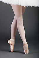 Low section of young female ballet dancer with legs crossed