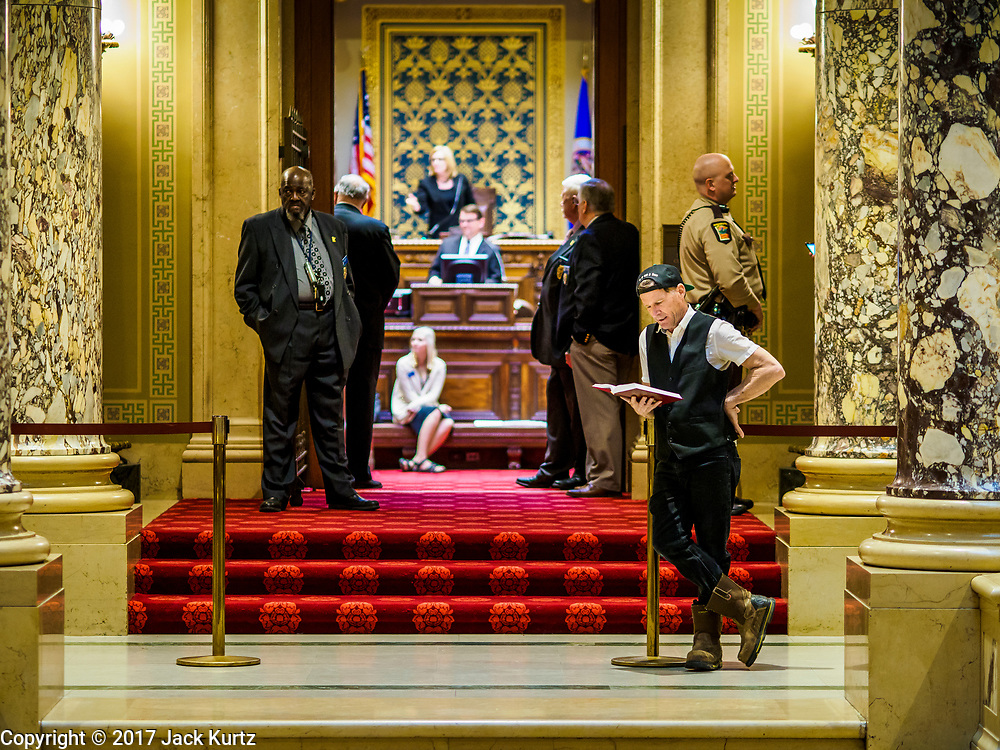 01 MAY 2017 - ST. PAUL, MN: JOHAN GALOO, right, who said he is running for mayor of Minneapolis, reads the bible in front of the Minnesota State Senate Chamber in the state capitol. About 300 people, representing immigrants' and workers' rights organizations, marched through the Minnesota State Capitol during a demonstration to mark May Day, International Workers' Day.      PHOTO BY JACK KURTZ
