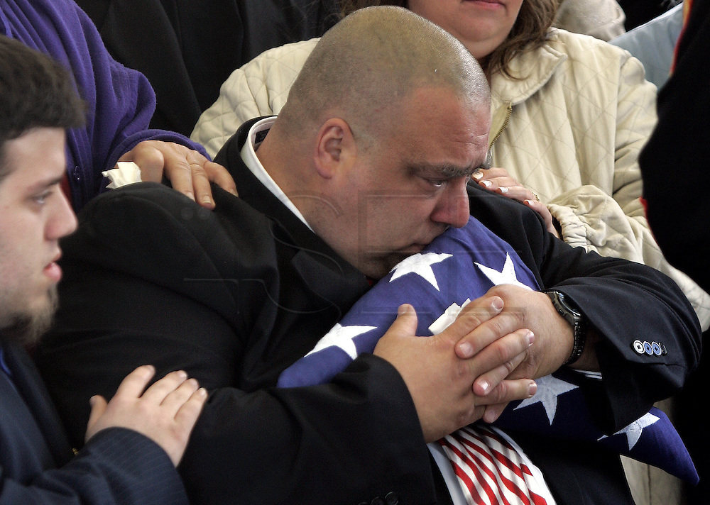 Joseph Ford Jr., left, comforts his father, Joshep Michael Ford Sr. as he kisses the flag that was folded and then given to him by the marines.  Funeral for Lance Cpl. Michael L. Ford a New Bedford marine that was killed in Iraq when the tank he was operating ran over an explosive device.  The funeral service was held at Church of Jesus Christ of Latter Day Saints in North Dartmouth, MASS and the burial was then held at the National Cemetary in Onset, MASS.