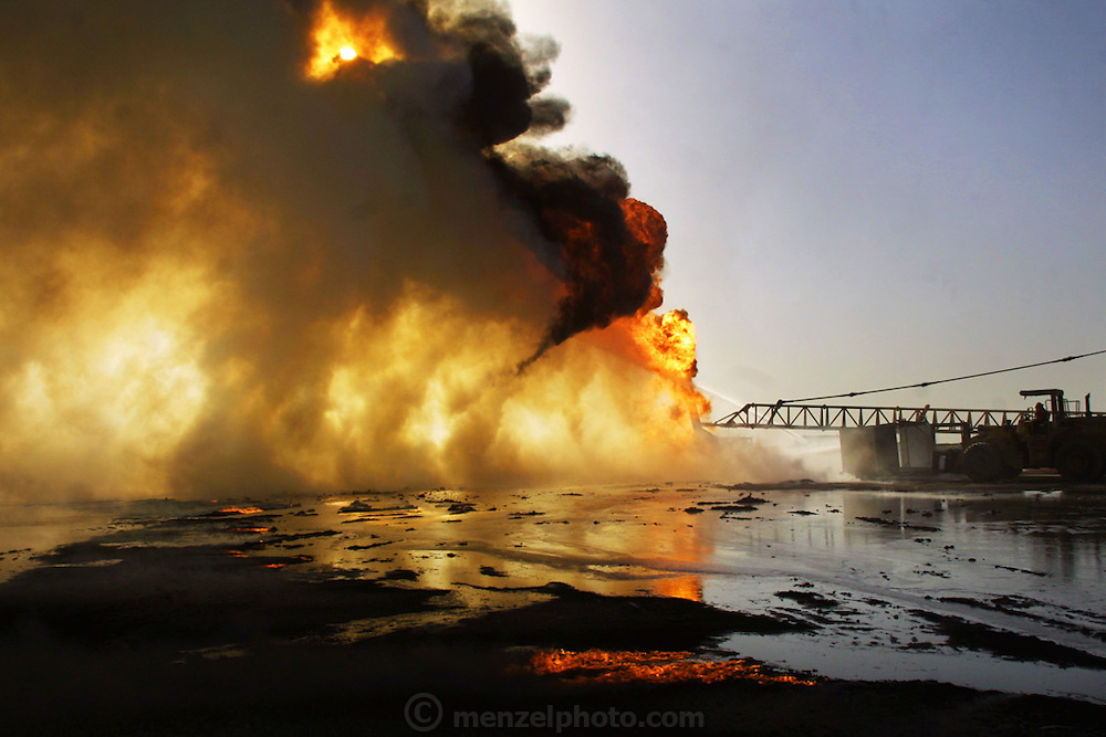 "Firefighters from the KWWK (Kuwait Wild Well Killers) attempt to extinguish an oil fire in the Rumaila Oil Field by guiding a ""stinger"" that will pump drilling mud into the flaming well. A ""stinger"" is a tapered pipe on the end of a long steel boom controlled by a bulldozer. Drilling mud, under high pressure, is pumped through the stinger into the well, stopping the flow of oil and gas. Many of the wells are 10,000 feet deep and produce huge volumes of oil and gas under tremendous pressure, which makes capping them difficult and dangerous. Rumaila, Iraq. Rumaila is also spelled Rumeilah."