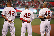 ANAHEIM, CA - APRIL 15:  (L-R) Mike Trout #27 of the Los Angeles Angels of Anaheim, Erick Aybar #2 of the Angels, and Albert Pujols #5 of Angels stand at attention during the playing of the National Anthem while wearing number 42 jerseys in honor of Jackie Robinson Day before the Los Angeles Angels of Anaheim against the Oakland Athletics at Angel Stadium on Tuesday, April 15, 2014 in Anaheim, California. The Athletics won the game 10-9 in eleven innings. (Photo by Paul Spinelli/MLB Photos via Getty Images) *** Local Caption *** Mike Trout;Erick Aybar;Albert Pujols