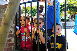 Kids munch on energy bars given out by volunteers as they wait in line for food distributed at St. Clare's Corner, established in Salinas by the Franciscan Workers of Junipero Serra in 1982. Supplied by the Food Bank of Monterey County, basic foodstuffs like rice and beans supplement family diets from October to May, the winter months when unemployment is highest.