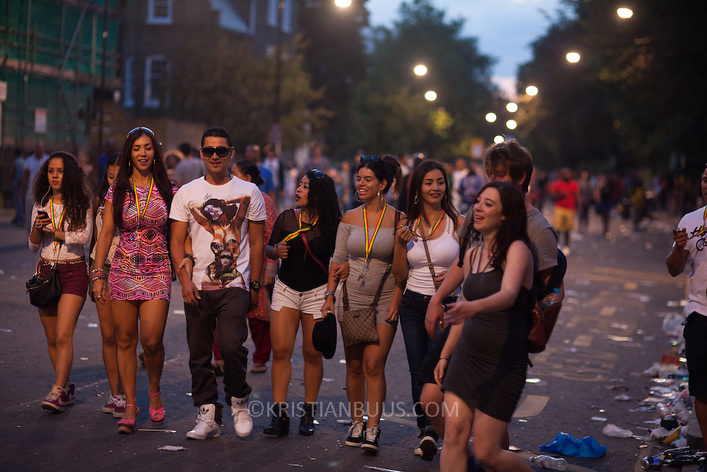 A group of very happy carnival goers heading back to Notting Hill tube station after a great day out. It is after sunset and the carnival is now officially over. The Notting Hill Carnival has been running since 1966 and is every year attended by up to a million people. The carnival is a mix of amazing dance parades and street parties with a distinct Caribbean feel.