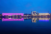Linz, Cultural Capital of Europe 2009. Lentos Kunstmuseum at the Danube, by Weber & Hofer architects/Zurich. The transparent facade is lit by lamps with varying colors. R.: Nibelungenbru?cke (bridge) and adjacent buildings, constructed during the Nazi rule.