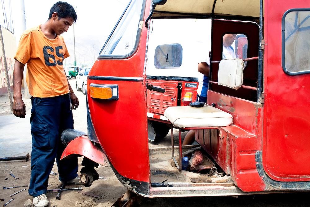 A man repairs a moto taxi on Tuesday, Apr. 14, 2009 in Ventanilla, Peru.