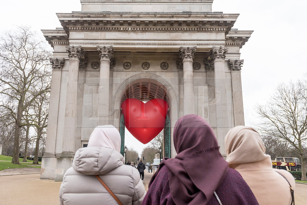 "© Licensed to London News Pictures. 14/02/2018. LONDON, UK. Tourists view a giant chubby heart balloon at Wellington Arc, part of ""Chubby Hearts Over London"", a design project conceived by Anya Hindmarch.  Supported by the Mayor of London, the British Fashion Council and the City of Westminster giant chubby heart balloons will be suspended over (and sometimes squashed within) London landmarks as a declaration of love to the city starting on Valentine's Day and continuing throughout London Fashion Week.   Photo credit: Stephen Chung/LNP"