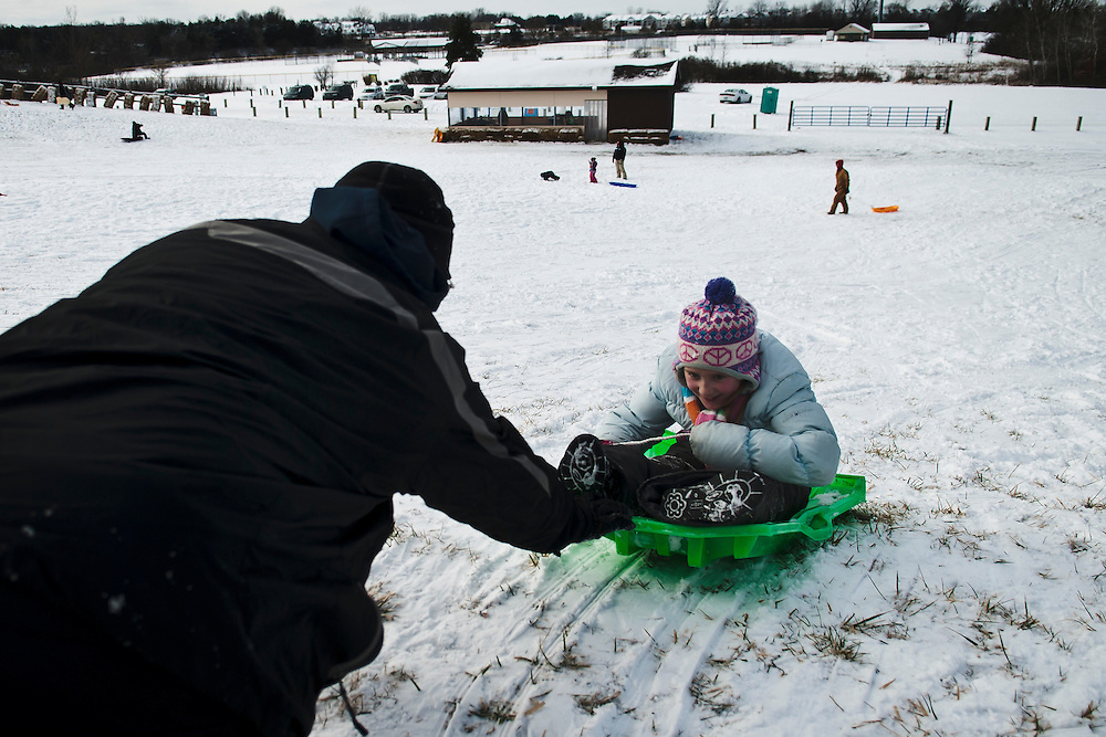 Lathan Goumas | The Flint Journal..January 14, 2012 - Ryan Trosen, of Holly, pushes his daughter Makenzie Trosen, 7, as she sits backwards in a sled at Creasey Bicentennial Park in Grand Blanc Township on Saturday.