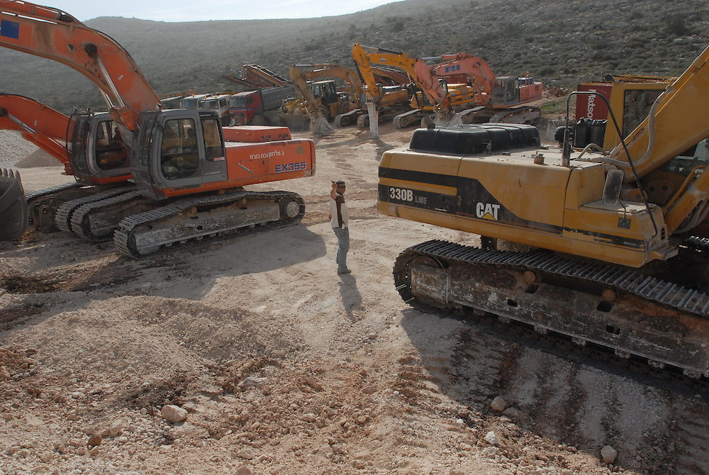 Heavy construction machines are parked in a large construction site in Beit Arye, where a new neighborhood was planned to be build. Civil Administration inspectors handed out a warrant to the site manger to stop construction in the site, following Israeli government decision to freeze construction in West Bank settlements for 10 months.