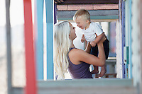 Young mother holding son (1-2) on outdoor porch