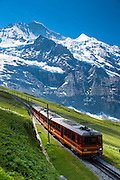 Jungfraubahn funicular train climbs to the Jungfrau from Kleine Scheidegg in the Swiss Alps in Bernese Oberland, Switzerland