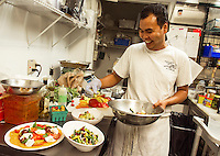 Jonathan Diola prepares dishes from Moulton Farm's summer bounty to accompany your Labor Day BBQ.  (l-r) Heirloom tomatoes with fresh mozzarella (Burrata) and basil, Mrs. Miner's 4 bean salad, potato salad with yellow and green squash are among his preparations Thursday morning.  (Karen Bobotas/for the Laconia Daily Sun)