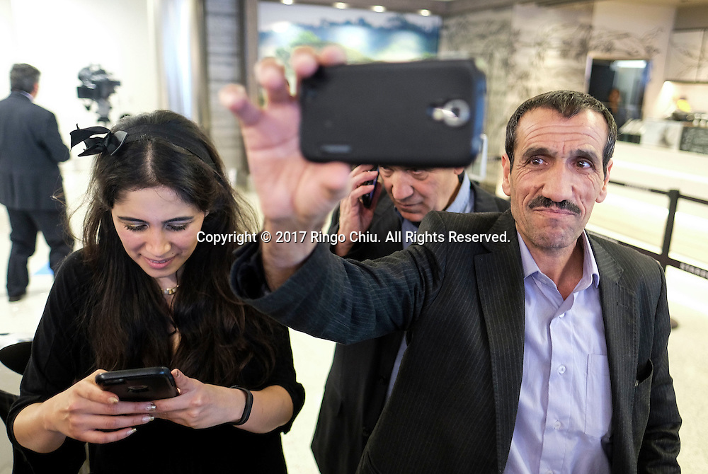 Ali Vayeghan, right, an Iranian citizen with a valid U.S. visa, takes selfie photos as he arrives at Los Angeles International Airport Thursday, Feb. 2, 2017. An Iranian man who was barred from entering the United States under President Trump&rsquo;s travel ban returned to Los Angeles on Thursday, the first person allowed into the country after a legal challenge to the White House&rsquo;s executive order.(Photo by Ringo Chiu/PHOTOFORMULA.com)<br /> <br /> Usage Notes: This content is intended for editorial use only. For other uses, additional clearances may be required.