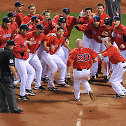 -Boston  MA, April 24, 2009-..Red Sox players surround Kevin Youkilis at home plate  after he walk-off home run off the Yankees Damaso Marte in the eleventh inning of the first game of the three-game series at Fenway Park.  ..(Photo by Michael Ivins/Boston Red Sox)