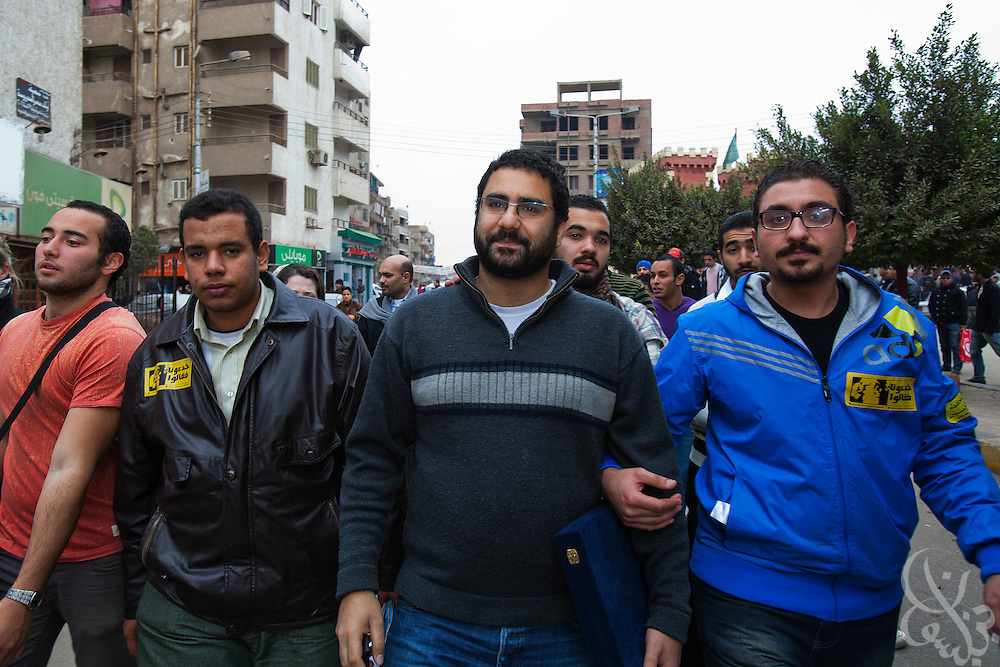 "Egyptian blogger Ala'a Abd El Fattah (C, glasses) participates with other youth activists in a brief march through the streets of Benha, Egypt January 18, 2012, calling for a return to Tahrir Square to continue the ""unfinished"" revolution. Fattah was jailed for 2 months last year by Egyptian authorities who claimed he had incited violence during protests, and since his release has been a champion of the protest movement and free speech."