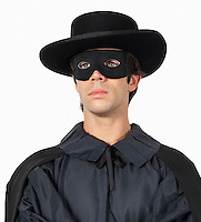 Thoughtful young man dressed as Zorro against gray background